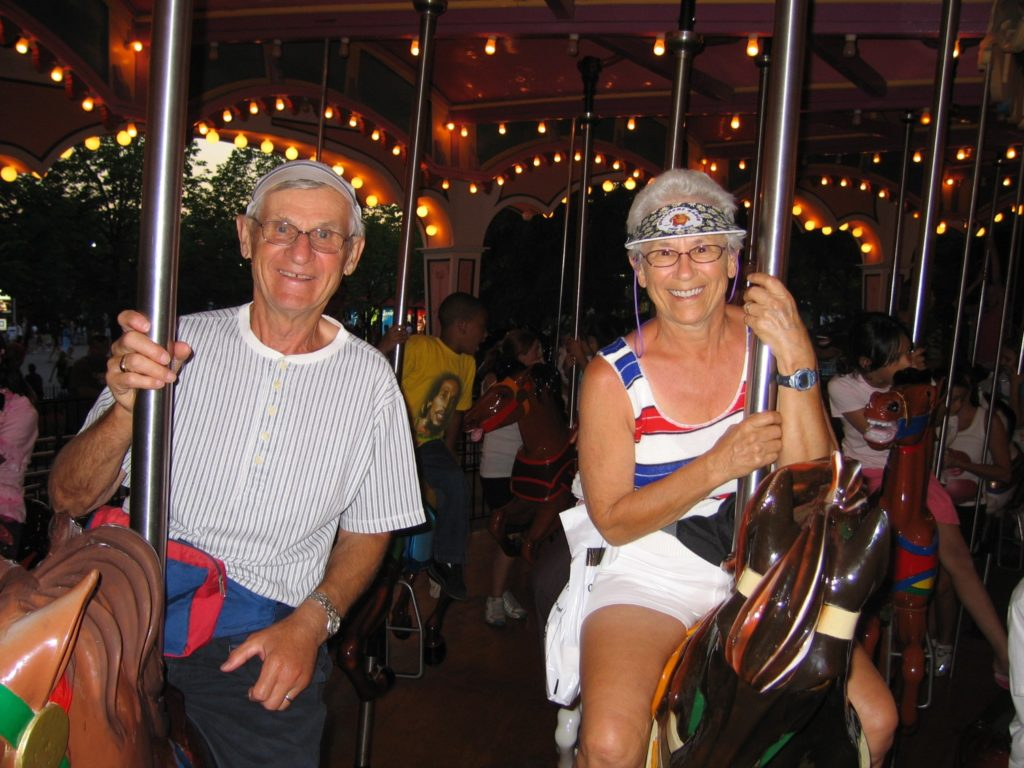 Rita and Peter Premich pose for a photo on a merry-go-round