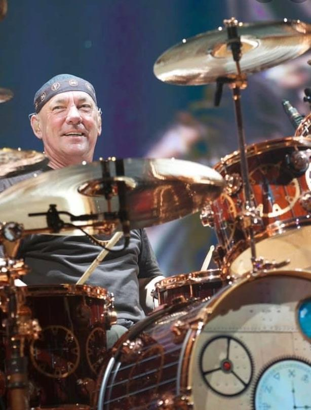 Neil Peart smiling and playing drums