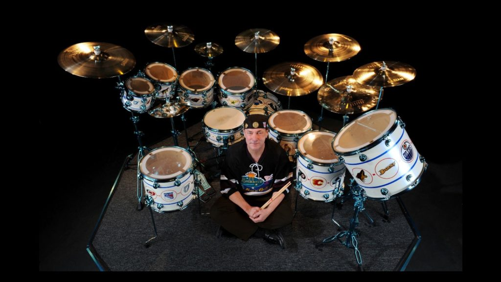 Neil Peart sitting in front of his drum kit