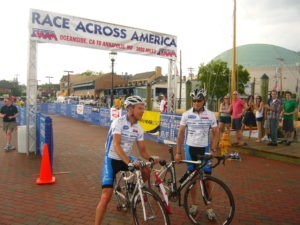 Men on bikes crossing the finish line